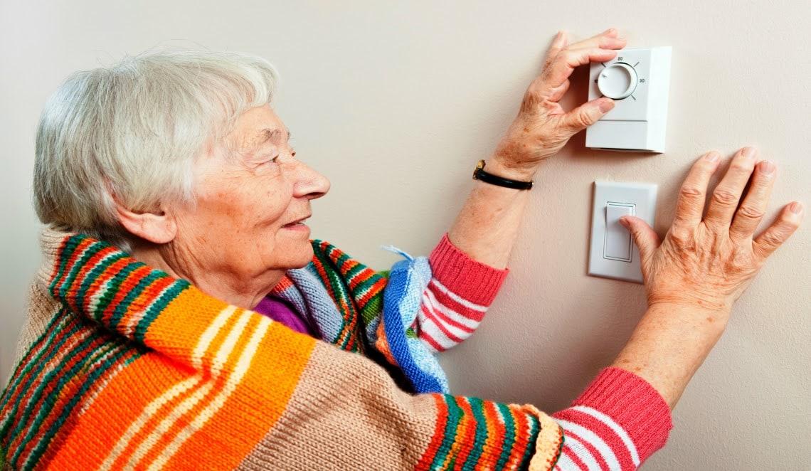 Senior Woman Adjusting Thermostat
